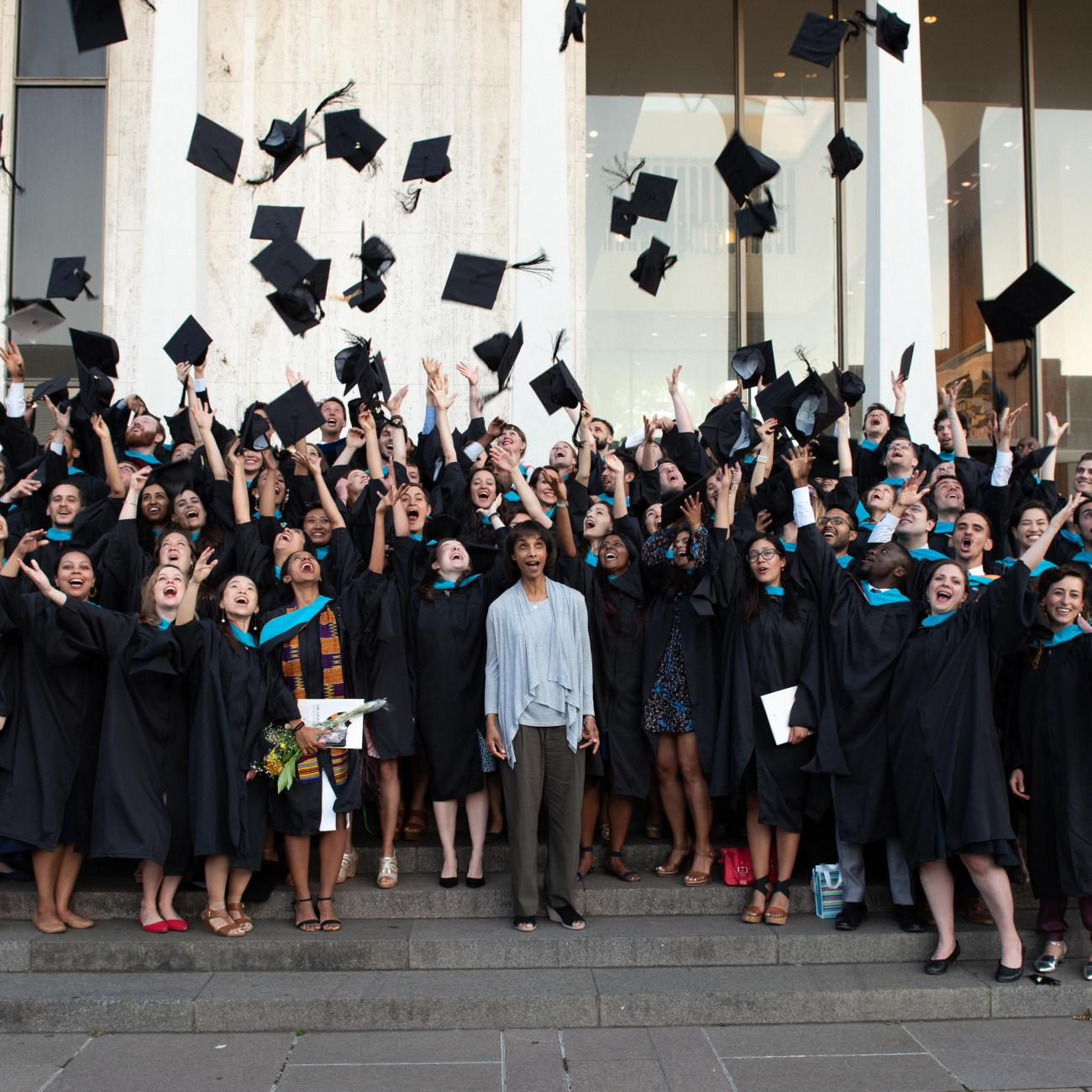 Graduating class throwing caps up in the air